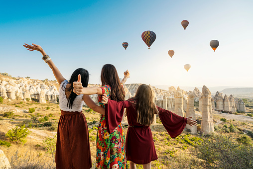 Traveling women looking at air balloons in sky in Cappadocia valley.